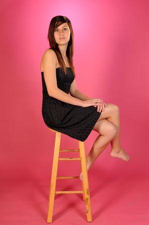 검은 strapless 드레스에 꽤 갈색 머리 십 대 소녀