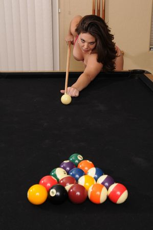 cue sticks: Adorable young brunette at the pool table Stock Photo