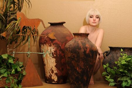 implied: Blonde sitting nude among vases and foliage