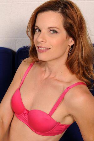 Beautiful mature redhead in a pink brassiere photo