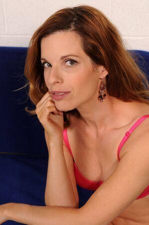 Beautiful mature redhead in a pink brassiere