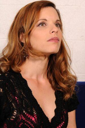 Beautiful mature redhead in a knit black top photo