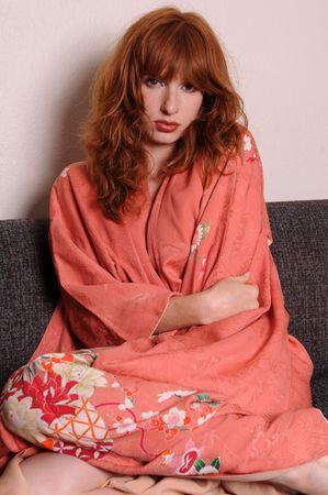 Beautiful redhead in a Japanese kimono on a gray couch Stock Photo