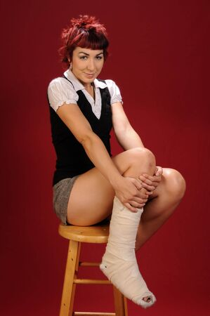 elfin: Elfin girl with punk red hair show off her bandaged foot Stock Photo