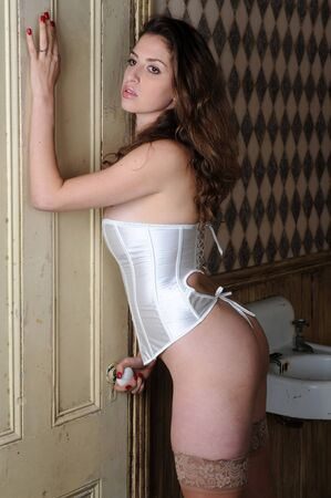 Beautiful brunette wearing a white corset in a dingy apartment photo