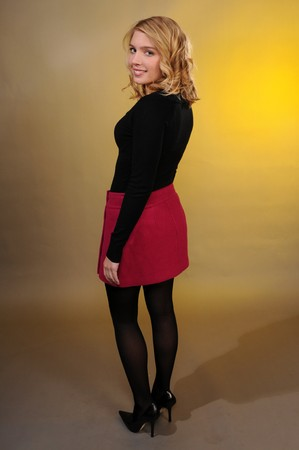 Pretty blonde teenager in a black sweater and a pink skirt photo