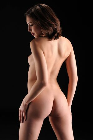 nude butt: Beautiful brunette standing nude against black
