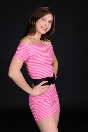 Beautiful brunette in a short pink striped dress