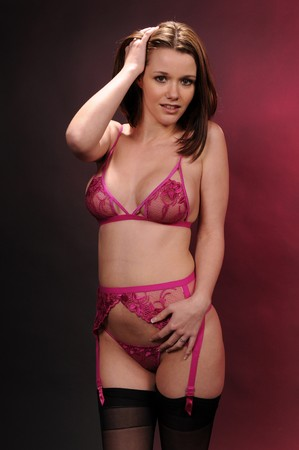 garter belt: Pretty young brunette in pink lingerie Stock Photo