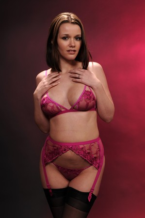 garter: Pretty young brunette in pink lingerie Stock Photo