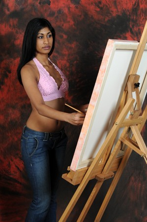 Beautiful young Indian woman working on a canvas photo