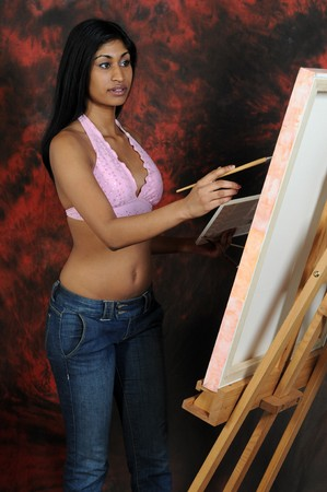indian paint brush: Beautiful young Indian woman working on a canvas Stock Photo