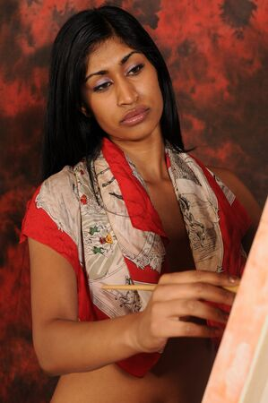 Beautiful young Indian woman working on a canvas Banco de Imagens