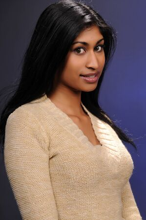 Beautiful young Indian woman in a beige knit blouse Banco de Imagens