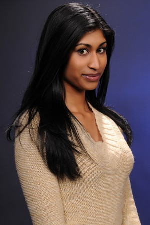 Beautiful young Indian woman in a beige knit blouse Stockfoto