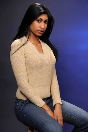 Beautiful young Indian woman in a beige knit blouse and blue jeans photo