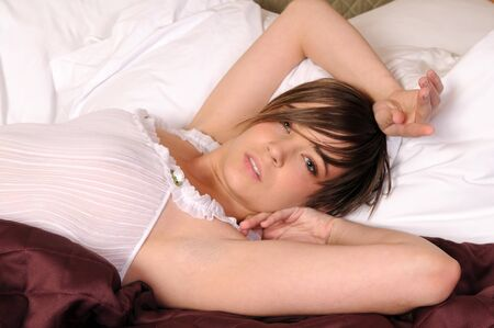 negligee: Young woman in bed in a white negligee Stock Photo