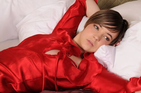 Young woman in bed in a red negligee photo