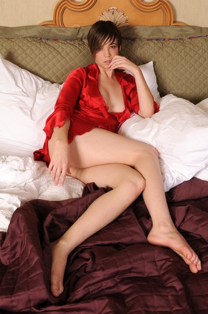negligee: Young woman in bed in a red negligee