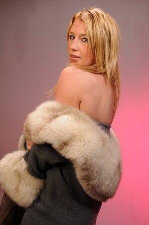 Beautiful statuesque blond posing nude in a fur trimmed coat Stock Photo - 4406469