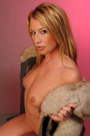nude blond: Beautiful nude blond in a fur trimmed coat Stock Photo