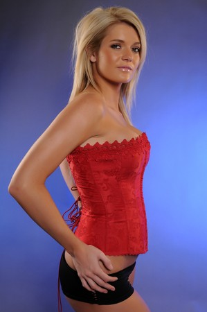 Beautiful statuesque blonde in a red bustier and black shorts photo