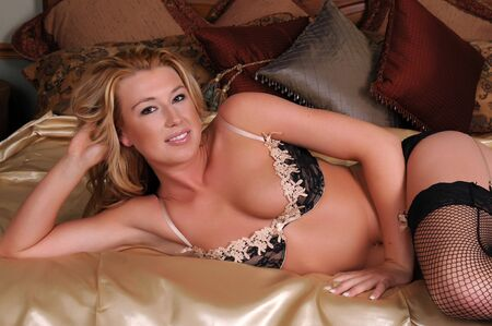 Statuesque blonde woman in lacy lingerie lying in bed photo