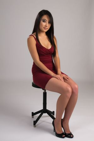 stool: Beautiful young Asian girl in a tight red violet dress