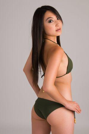 Beautiful young Asian girl in a dark green bikini