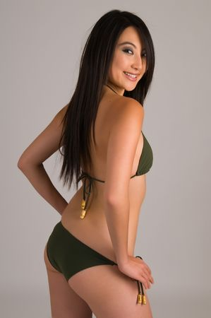 Beautiful young Asian girl in a dark green bikini