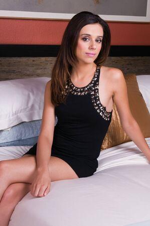 Slender young brunette in a little black dress photo