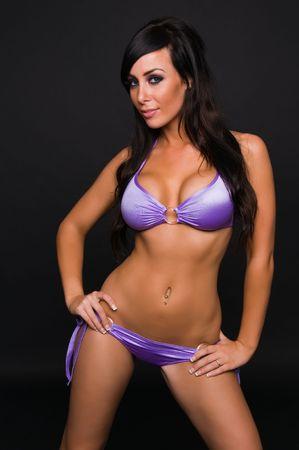 Beautiful young brunette in a purple bikini