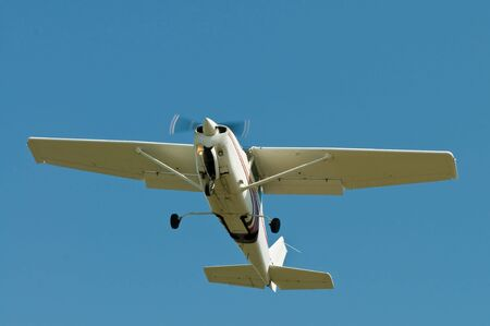 Small plane flying overhead against a blue sky