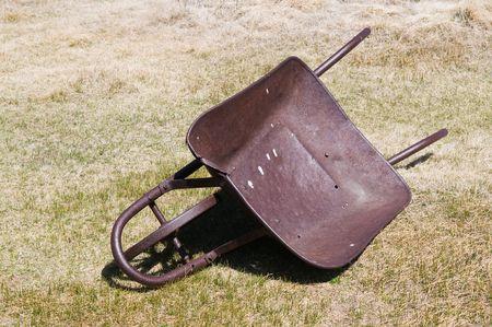 Old wheelbarrow lying abandoned in dry grass Stock Photo - 4883424