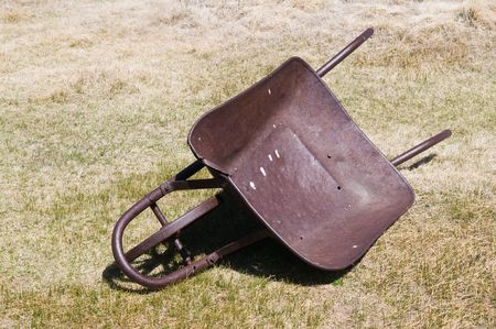 Old wheelbarrow lying abandoned in dry grass Stock Photo - 4883424