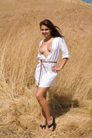 Lovely young brunette in a field of dry brown grass Stock fotó