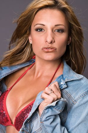 Petite brown haired beauty in a shiny red bikini and denim jacket photo