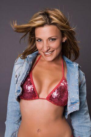 bikini slender: Petite brown haired beauty in a shiny red bikini and denim jacket