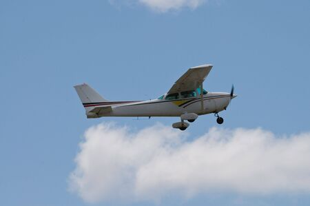 small plane: Small plane flying against a cloudy sky Stock Photo