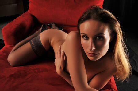 Beautiful Russian woman nude on a red couch Stock Photo - 5160306