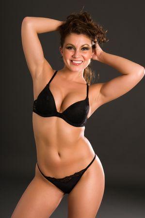 Beautiful young brunette dressed in black lingerie Banco de Imagens
