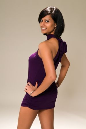 middle eastern woman: Pretty young Middle Eastern woman in a purple mini dress Stock Photo