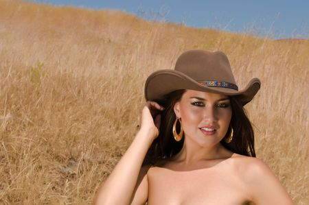 american sexy: Lovely young brunette in a field of dry brown grass Stock Photo