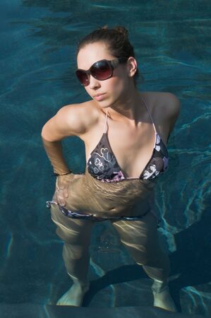 Pretty young brunette in a bikini in a swimming pool