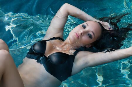 Pretty young brunette floating in a swimming pool photo