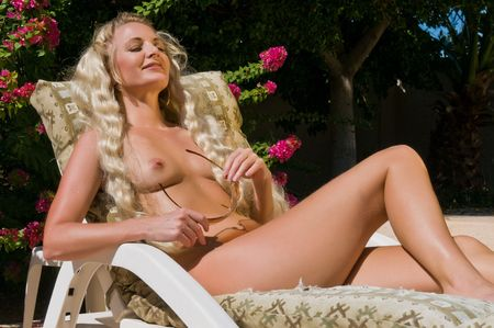Beautiful mature blonde getting an all over tan by the pool Stock Photo - 5773268