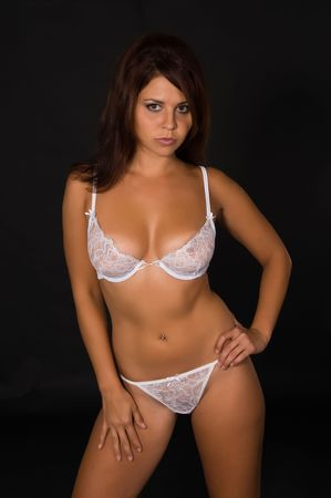 white panties: Lovely young brunette in white lingerie on a black background