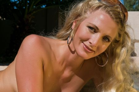 Beautiful mature blonde getting an all over tan by the pool Stock Photo - 5787362