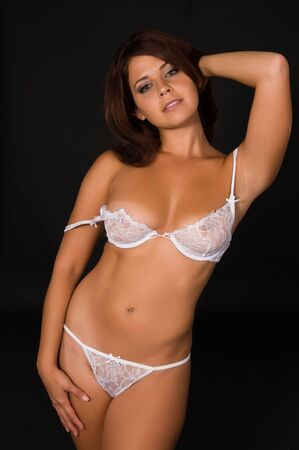petite: Lovely young brunette in white lingerie on a black background