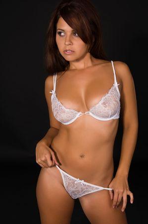 panties: Hermosa morena joven en ropa interior blanca sobre un fondo negro Foto de archivo